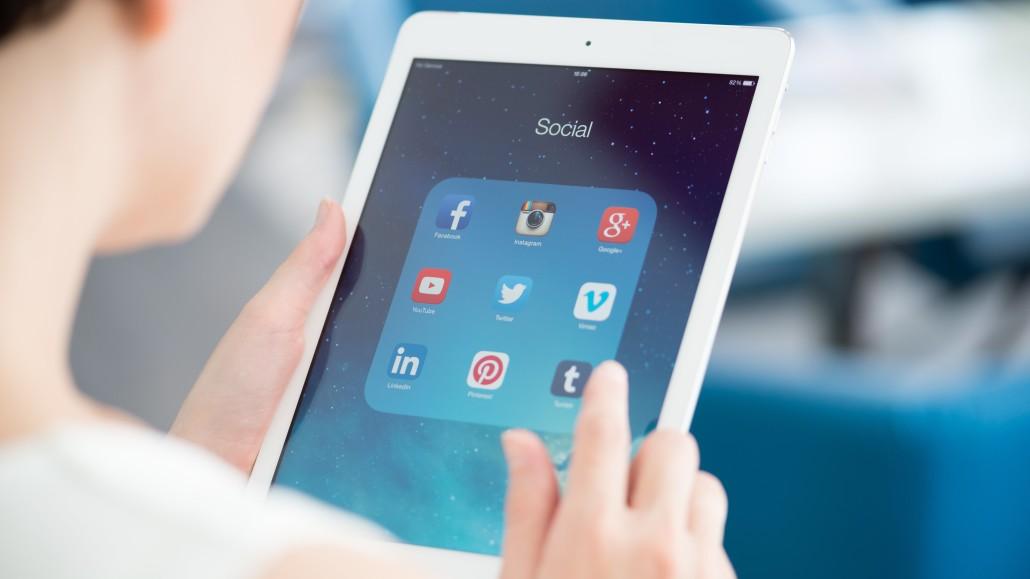 kvinna håller surfplatta, sociala medier, word of mouth